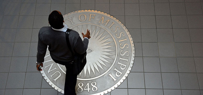 Student walking over the university seal in Martindale Hall